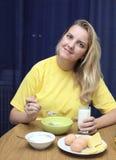 Girl eats a porridge with milk Stock Image
