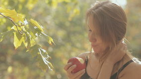 The girl eats a red apple in the forest. Close up of a girl who eats a red apple in the forest stock footage