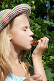Girl eats red currant in the garden Stock Image