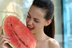 Girl eats red ripe watermelon. Girl with pleasure eats red ripe watermelon Royalty Free Stock Photos