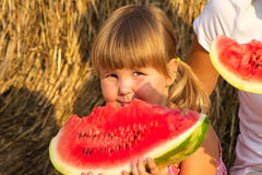 Girl eats red tasty water-melon Royalty Free Stock Images