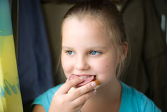 The girl eats a sandwich with sausage Royalty Free Stock Photo