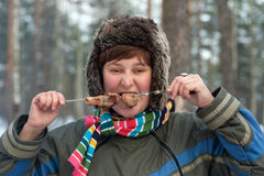 The girl eats a shish kebab Royalty Free Stock Photos