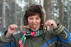 The girl eats a shish kebab Royalty Free Stock Photos