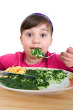 Girl eats spinach Stock Photography