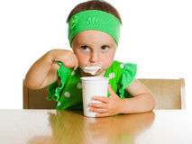 Girl eats with a spoon dairy product. Stock Photos