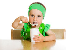 Girl eats with a spoon dairy product. Royalty Free Stock Photo