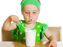Girl eats with a spoon dairy product. Royalty Free Stock Image