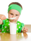 Girl eats with a spoon dairy product. Stock Images