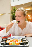 Girl eats sushi Royalty Free Stock Photography