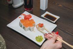 The girl eats sushi, the Japanese sticks at the Japanese restaurant. Royalty Free Stock Images