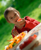 The girl eats a tomato. The little girl sits at a table on a verandah and eats fresh vegetables Stock Photo