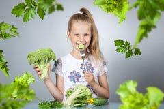 Girl eats vegetables Stock Image