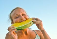 Girl eats yellow watermelon Stock Image