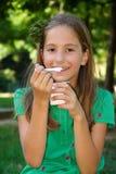 Girl eats yogurt Stock Photography