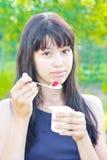 Girl eats yogurt Stock Photos