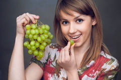 The girl is eatting the green grapes Royalty Free Stock Photo