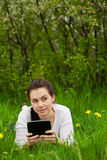 Girl with ebook lying on the grass Royalty Free Stock Photos