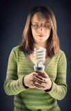 Girl with eco light bulb Royalty Free Stock Images