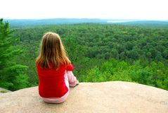 Girl edge cliff. Young girl sitting on an edge of a cliff Stock Photos