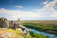 A girl on the edge of a cliff. A girl on the edge of a cliff above a river. A woman is sitting on the top of a cliff. Active lifestyle. A tourist on the Royalty Free Stock Photos