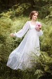 Girl on the edge of the forest in a long white dress Stock Photography