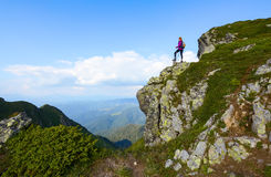 Girl at the edge of precipice high on the mountains. Royalty Free Stock Images
