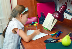 Girl at the educational table Stock Images