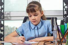 A girl of eight years old is concentrating writing with a fountain pen sitting at a table in an office stock images