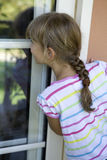 Girl eight years old look through window Royalty Free Stock Image