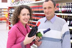 Girl and elderly man in shop with wine bottles Royalty Free Stock Image