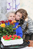 Girl with elderly woman. Girl kissing elderly woman on holiday Royalty Free Stock Photo