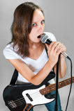 Girl with electric bass guitar  on gray Stock Photo