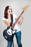 Girl with electric bass guitar  on gray Royalty Free Stock Photography