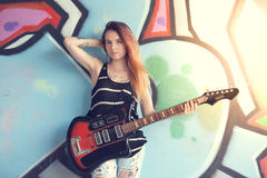 Girl with electric guitar stands near the wall of graffiti. Girl teen with electric guitar stands near the wall of graffiti Royalty Free Stock Photos
