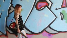 Girl with electric guitar walking along the graffiti wall. HD stock video footage