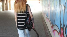 Girl with electric guitar walking along the graffiti wall. Girl with electric guitar walking along the graffiti wall and turns stock video footage