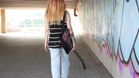 Girl with electric guitar walking near the graffiti wall. stock video