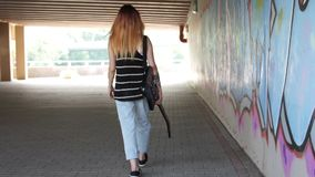 Girl with electric guitar walking near the graffiti wall. Girl with electric guitar walking near the graffiti wall and turns. She is part of a frame on the left stock video