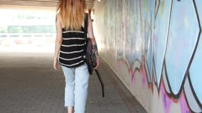 Girl with electric guitar walking near the graffiti wall. Girl with electric guitar walking near the graffiti wall and turns. She is part of a frame on the stock video