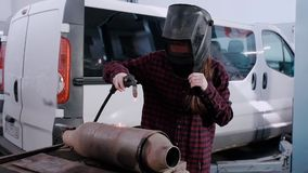 The girl-electric welder. The girl in a plaid shirt and a protective helmet of an electric welder welds metal on a car. Silencer against the background of a car stock video