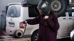 The girl-electric welder. The girl in a plaid shirt and a protective helmet of an electric welder welds metal on a car. Silencer against the background of a car stock footage