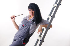 Girl electrician. A young girl electrician in a overall with screwdriver Royalty Free Stock Image