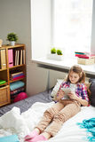 Girl with electronic book. Pretty schoolgirl with ponytails resting on bed and reading electronic book Stock Photo