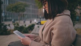 Girl with electronic book reader on street. A beautiful brunette student in trendy glasses rests in tranquility while reads through the imaginative and stock footage