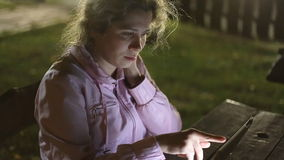 Girl with the electronic tablet sitting on a bench. Girl student electronic tablet sitting on a bench in the park stock footage