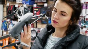 Girl in the electronics store chooses gray drone. Young girl in the electronics store chooses gray drone. She carefully examines the quadcopter before buying. On stock footage