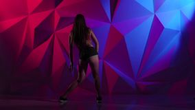 Girl elegant dance twerk in shorts on bright graphic background. Slow motion stock video