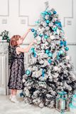 Girl in elegant dress is decorated with Christmas tree royalty free stock images