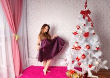 Girl in an elegant dress near a fir-tree Royalty Free Stock Image